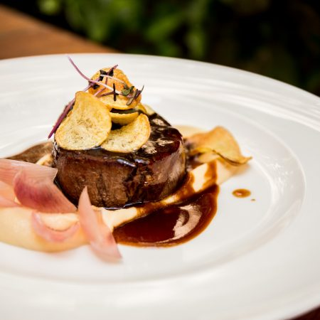 Beef tenderloin steak with red wine sauce, parsnip and pickled onion